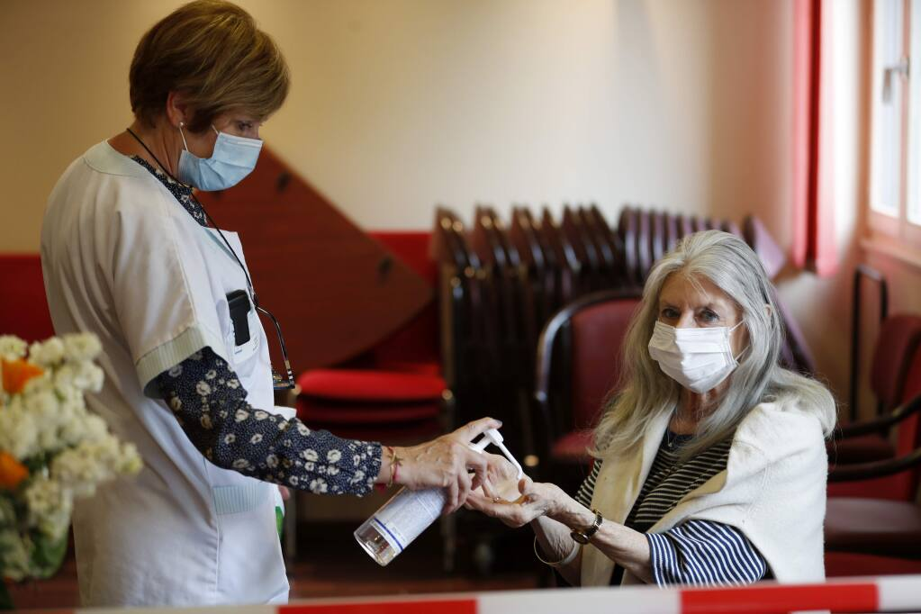 An employee sprays alcoholic gel on Josiane Cohen, right, before meeting her daughter Laetitia at the Kaysersberg nursing home, eastern France, Tuesday April 21, 2020. France banned all nursing home visits early in the pandemic, and many residents have been confined to their rooms for weeks, because the coronavirus has been especially dangerous for the elderly. France made an exception to its strict virus confinement measures to allow families to visit relatives in nursing homes since Monday. (AP Photo/Jean-Francois Badias)