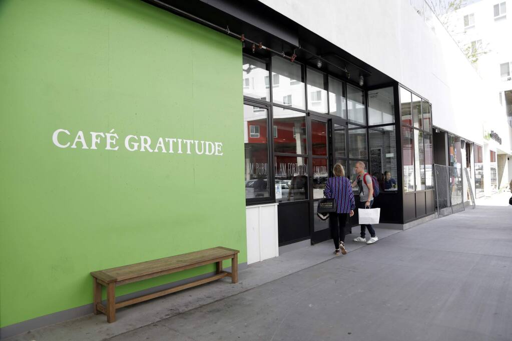 This Wednesday, May 4, 2016 photo shows Cafe Gratitude restaurant in Los Angeles. At the Cafe Gratitude restaurant chain in California, waiters serve plates of vegan rice bowls, vegetable pizzas and tempeh sandwiches with names like 'Gracious,' ''Warm-Hearted' and 'Magical.' Angry patrons and animal rights activists are calling on vegans to boycott the restaurant after learning that owners Matthew and Terces Engelhart have begun eating meat and consuming animals raised on their private farm. (AP Photo/Nick Ut)
