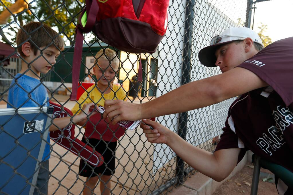Young Prune Packers fans Ethan Newton, 6, left, and Chase Desmond, 5, get autographs from pitcher Matt Campbell during the Healdsburg Prune Packers baseball game against the Humboldt Crabs, in Healdsburg, California on Wednesday, June 22, 2016. (Alvin Jornada / The Press Democrat)