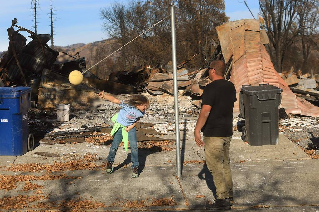 Louis Pell and his eight-year-old daughter Lilly, in front of their burned home, Tuesday Nov. 7, 2017 in Santa Rosa's Coffey Park. (Kent Porter / The Press Democrat) 2017
