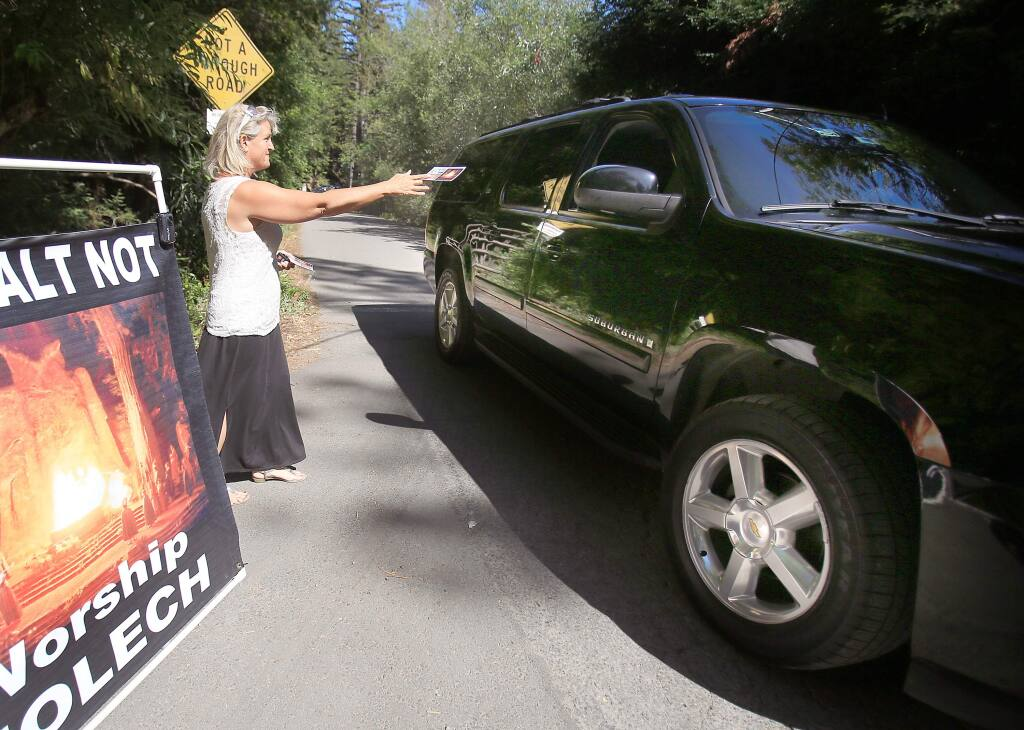 Christine Weick hands out literature at the entrance to the Bohemian Grove in Monte Rio Friday July 17, 2015 in Santa Rosa. (Kent Porter / Press Democrat) 2015