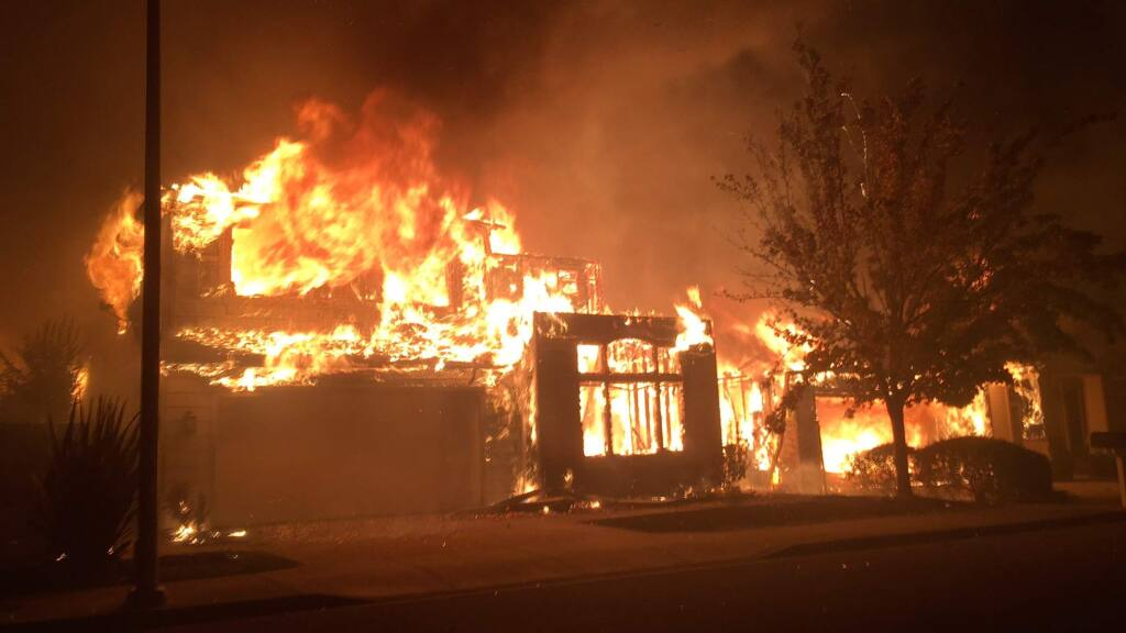 Fire burns a home in the Fountaingrove area of Santa Rosa behind the Home Depot store on Monday, Oct. 9, 2017. (KENT PORTER/ The Press Democrat)