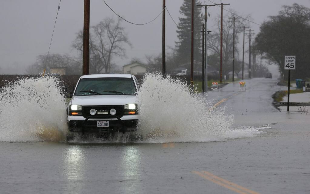 A truck navigates through water along Lytton Station Road, which was closed due to flooding, in Healdsburg on Tuesday, February 26, 2019. (Christopher Chung/ The Press Democrat)