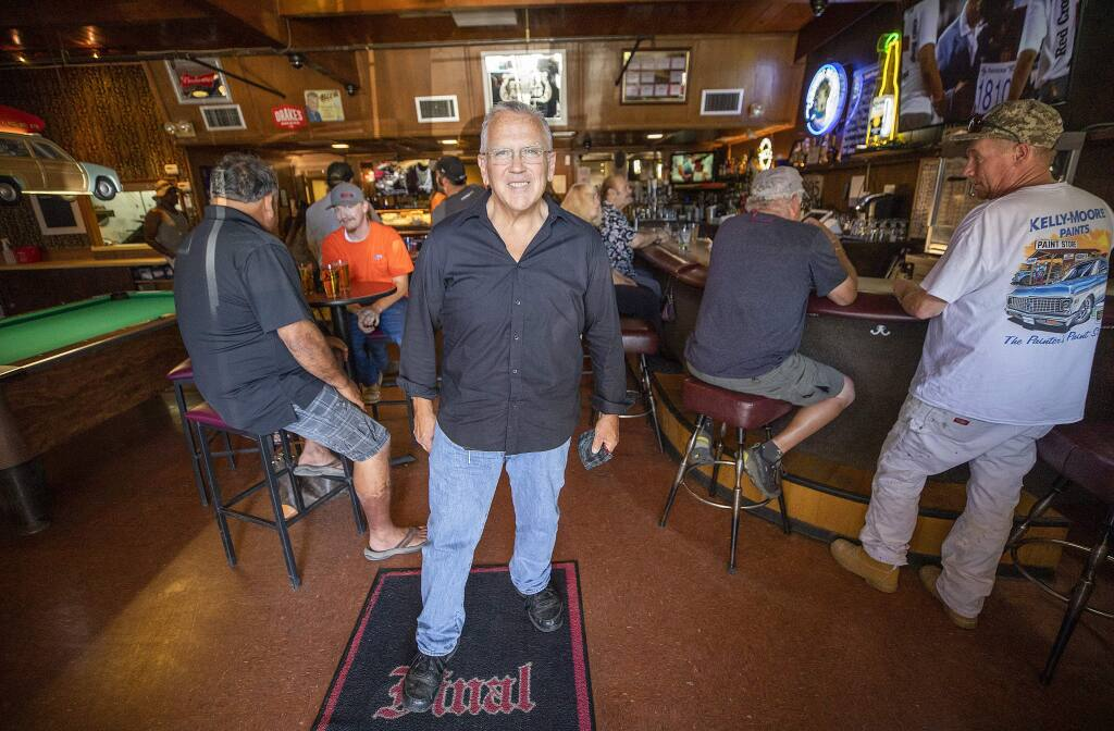 """John Timberlake bought the Final Edition Bar & Grill in the Larkfield Shopping Center the year before the Tubbs fire and has since experienced power outages, another wildfire, and now 'the virus apocalypse,"""" but he struggles on. (photo by John Burgess/The Press Democrat)."""