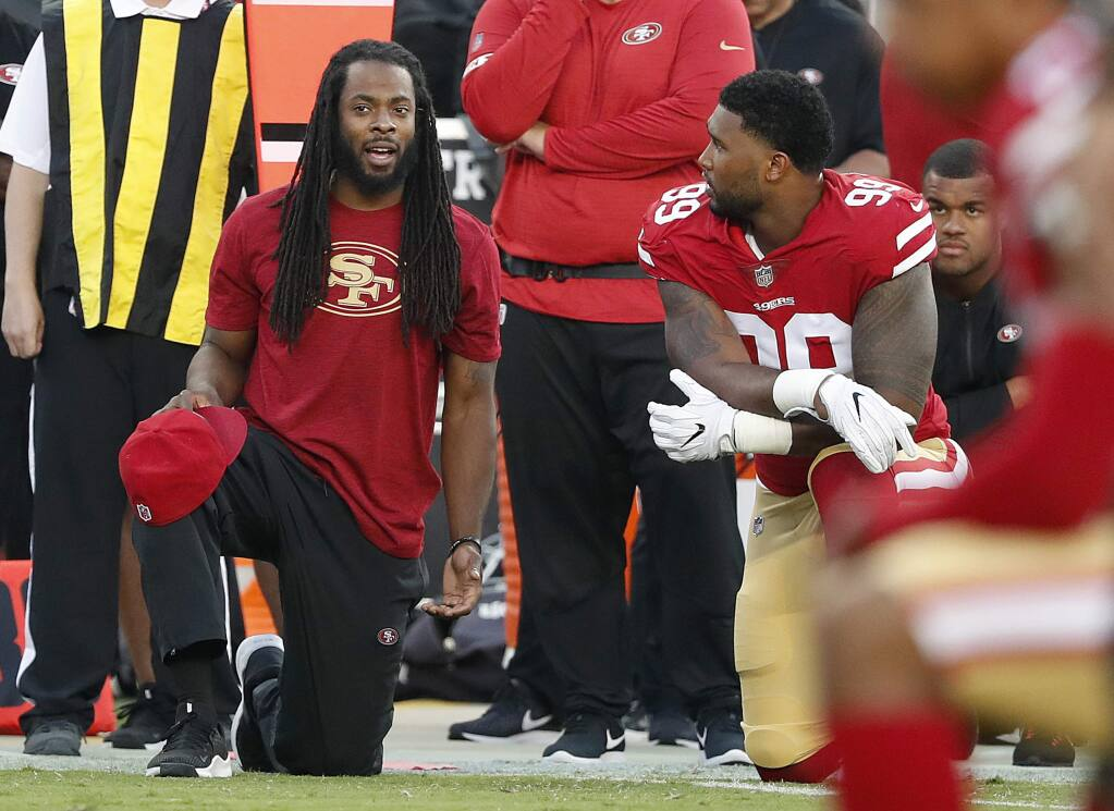San Francisco 49ers defensive back Richard Sherman, left, watches from the sideline with defensive end DeForest Buckner during the first half of the team's preseason game against the Dallas Cowboys in Santa Clara, Thursday, Aug. 9, 2018. (AP Photo/Tony Avelar)