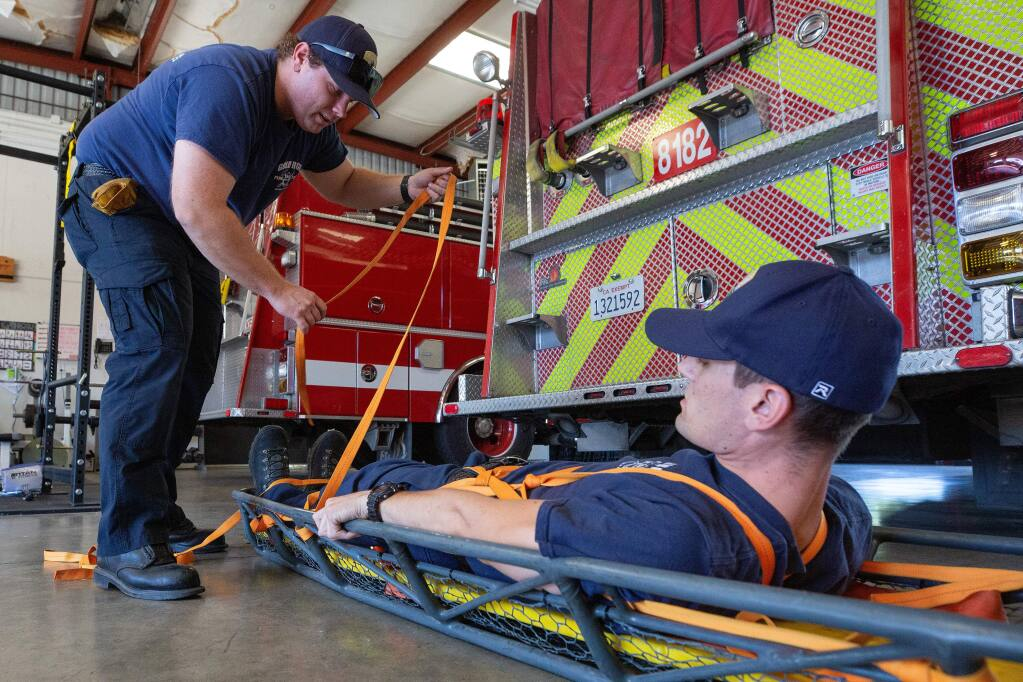 Gold Ridge intern firefighter Alex Gardner, left, trains with firefighter Konner Andrade on how to a patient into a Stokes basket, which is used rescue situations, at Gold Ridge Fire Protection District Station #2, in the Twin Hills community of Sebastopol, California, on Wednesday, October 9, 2019. (Alvin Jornada / The Press Democrat)