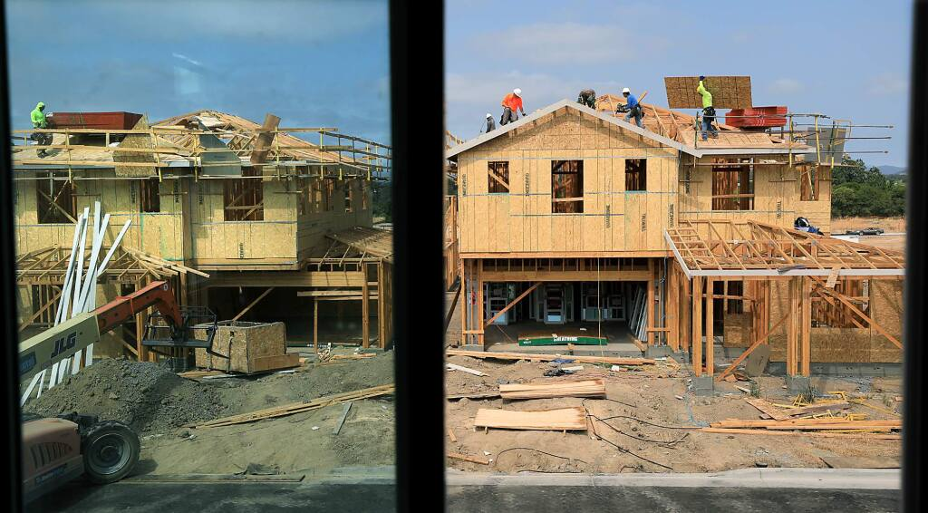 Workers place plywood on the roofs of homes, Tuesday, July 3, 2018 at the Fox Hollow subdivision in Santa Rosa. Irvine-based developer City Ventures has begun building the first of 143 singe family homes off Fulton Road. (Kent Porter / The Press Democrat) 2018