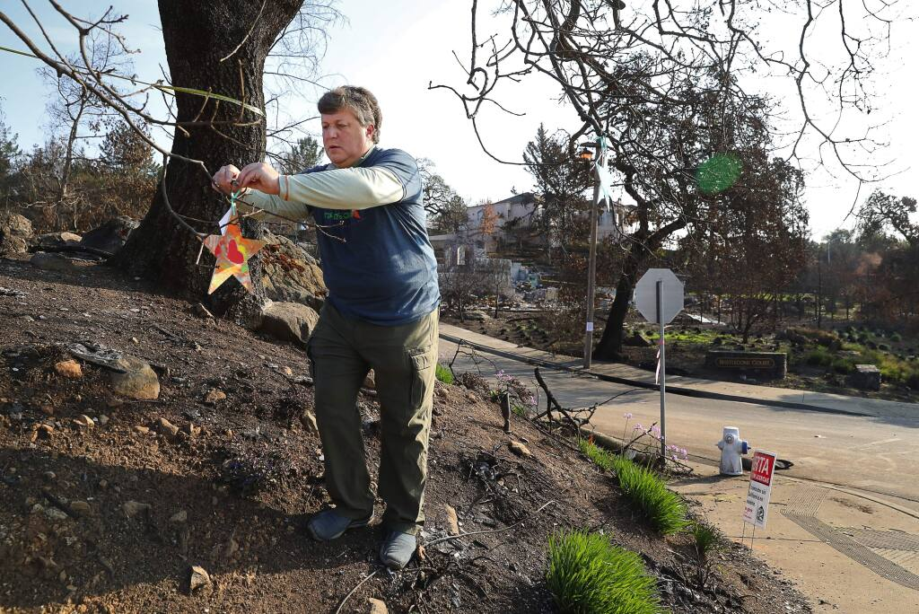 Jeff Parness, founder of Stars of HOPE, hangs a handpainted star on the corner of Fir Ridge Drive and Bristlecone Court, in the Fountaingrove area of Santa Rosa on Wednesday, December 13, 2017. (Christopher Chung/ The Press Democrat)