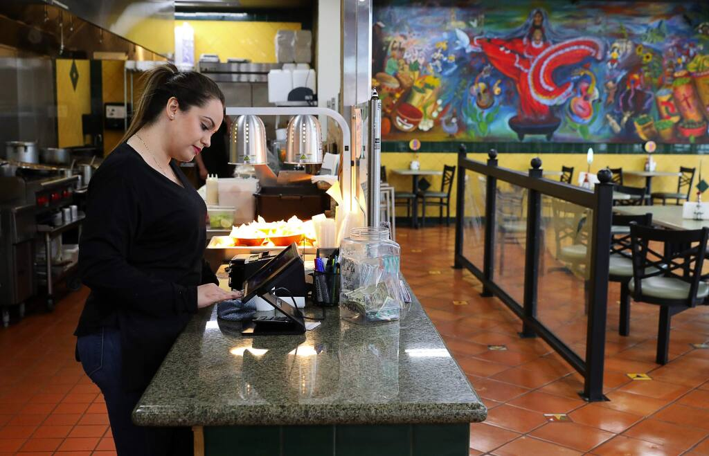 Carolina Padilla, a 22-year-old SSU student, works the register at Pepe's Mexican Restaurant, in the Roseland area of Santa Rosa on Wednesday, January 17, 2018. (Christopher Chung/ The Press Democrat)