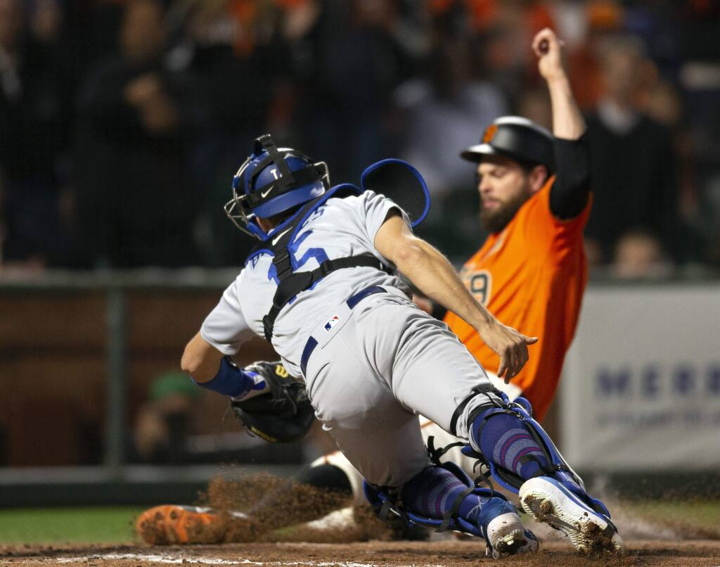 Los Angeles Dodgers catcher Austin Barnes dives too late to tag out the San Francisco Giants' Brandon Belt, who scored from second on a single by Kevin Pillar during the sixth inning Friday, June 7, 2019, in San Francisco. (AP Photo/D. Ross Cameron)