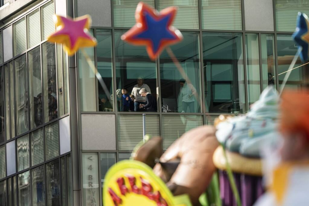 People watch the balloons moving along Sixth Avenue from an office during the Macy's Thanksgiving Day Parade in New York, Thursday, Nov. 28, 2019, in New York. (AP Photo/Jeenah Moon)