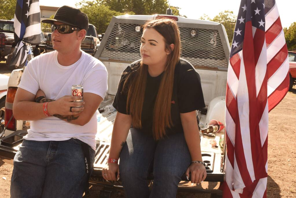 Tractor pulls fans Bryce Tutty, 21, and Taylor Short, 18, relax on a pickup truck during the West Coast Diesels 4th Annual Tractor Pulls and Show & Shine held Saturday at Sonoma County Fairgrounds in Santa Rosa, California. September 7, 2019.(Photo: Erik Castro/for The Press Democrat)