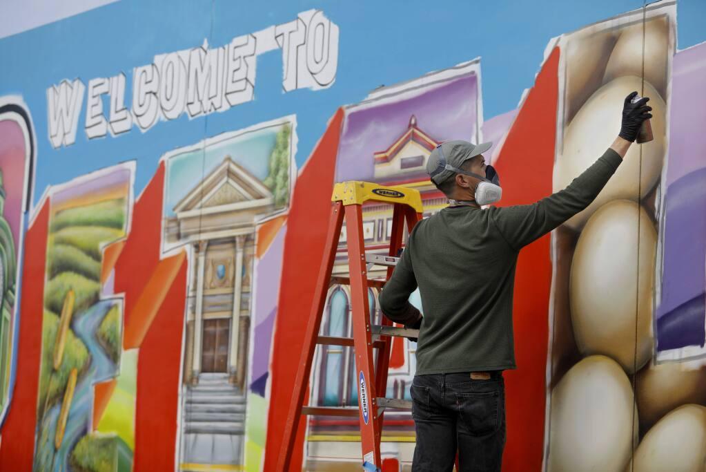 Mural artist Maxfield Bala applies spray paint to his 'Welcome to Petaluma' mural project on Petaluma Blvd South along Highway 101 in Petaluma on Monday, January 28, 2019. (BETH SCHLANKER/ The Press Democrat)