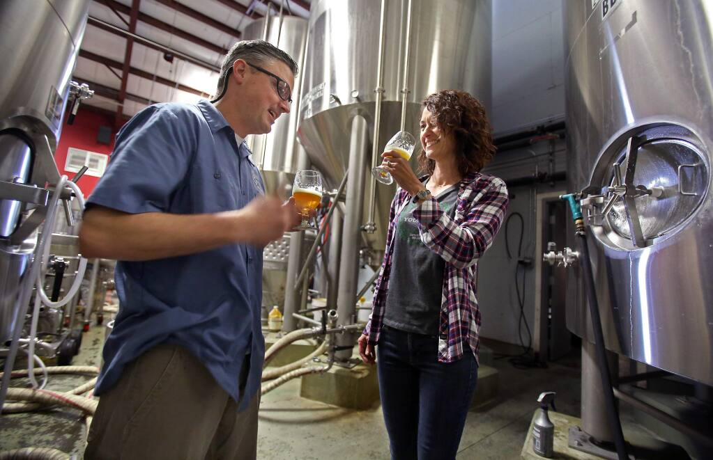Russian River Brewing Company co-owners Vinnie and Natalie Cilurzo sample Pliny the Younger at the brewing facility in Santa Rosa on Thursday, February 5, 2015. (Christopher Chung/ The Press Democrat)