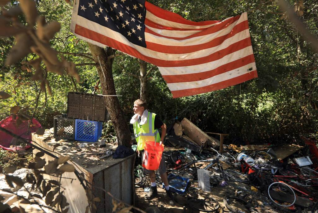 A worker from Catholic Charities looks for salvageable tools, Monday August 14, 2017 at Homeless Hill at the Farmers Lane extension in Santa Rosa, after city personnel relocated the residents of the homeless encampments. Hazardous waste, feces, food, household furnishings, bikes and thousands of pounds of clothes and other debris are being removed from the site. (Kent Porter / The Press Democrat) 2017