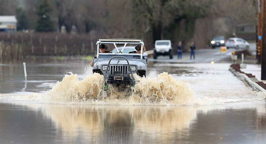 A motorist with a lifted vehicle drives through roadblocks on Highway 128 at the Alexander Valley Bridge, Monday Jan. 9, 2017. Earlier in the day, several rescues took place for those getting stranded in the water as the Russian River went over flood stage. (Kent Porter / The Press Democrat) 2017