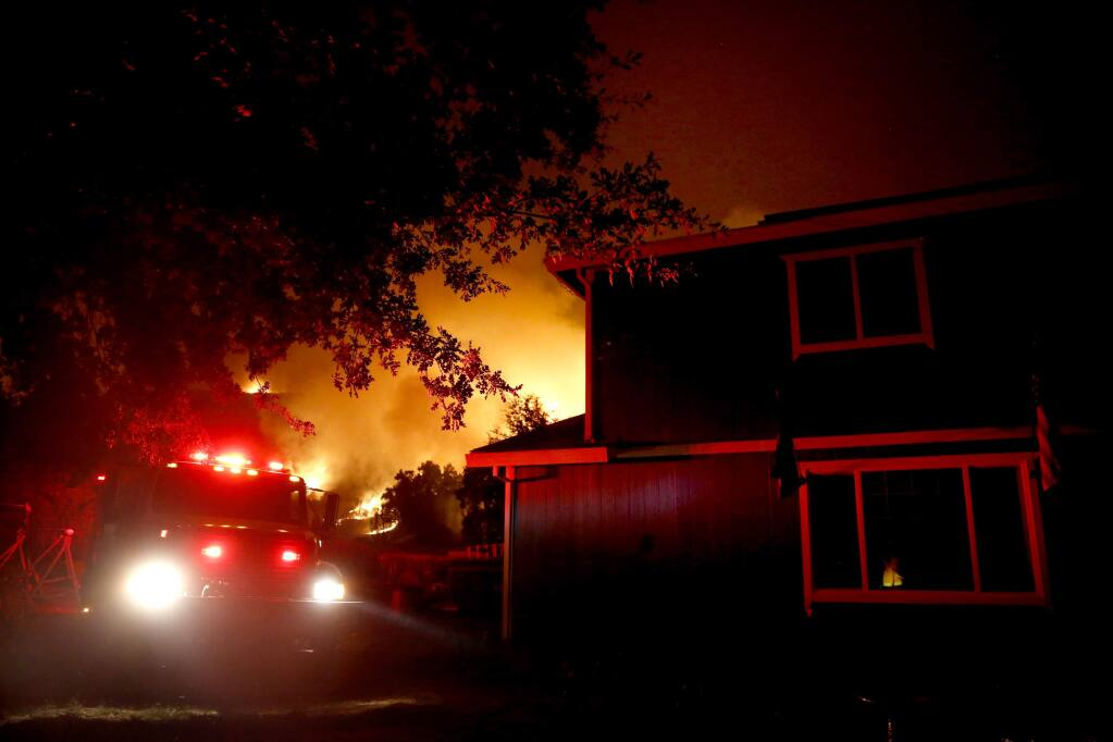 A firetruck sits parked near a residence while the Ranch Fire, part of the Mendocino Complex fires, burns in Upper Lake on Sunday, July 29, 2018. (Beth Schlanker/ The Press Democrat)