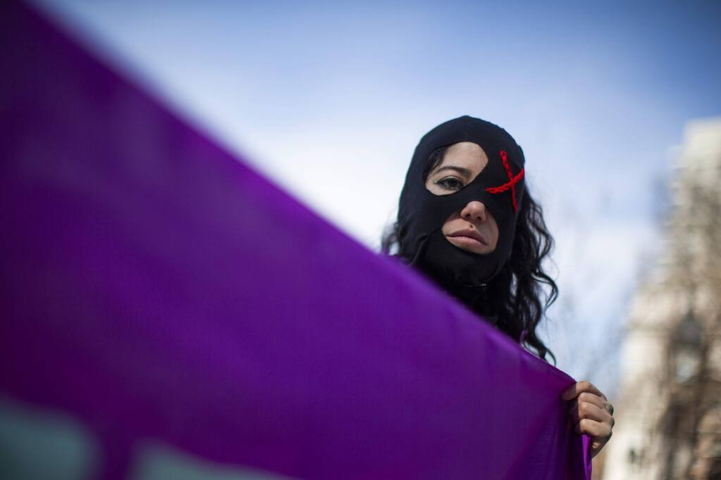 A woman holds as flag as people participate in a rally celebrating International Women's Day at Washington Square Park in New York, Sunday, March 8, 2020.(AP Photo/Eduardo Munoz Alvarez)