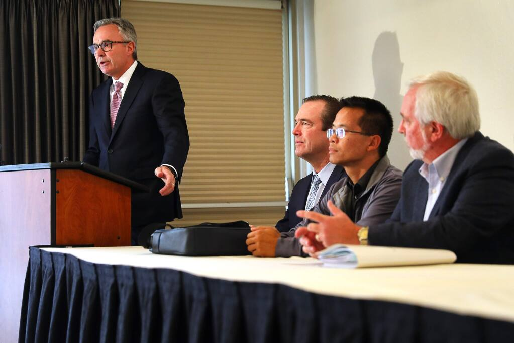 Attorney Greg Bentley, of Bentley & More, LLP, left, addresses the media during a press conference announcing a lawsuit by a group of fire victims against AAA for systematically underinsuring their homes and leaving them short of rebuilding costs, while attorney Christopher Kreeger, and plaintiffs Matt Quan and Larry Spanier listen, in Santa Rosa on Tuesday, December 18, 2018. (Christopher Chung/ The Press Democrat)