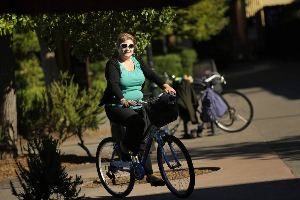 Sonoma County Bicycle Coalition Commuter of the Year, Liz Klaproth, rides home from work in downtown Sebastopol on Friday, July 11, 2014. Klaproth has rode her bike to work everyday for the past five years. (Conner Jay/The Press Democrat)