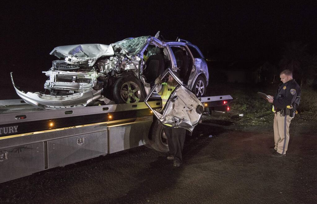 As the mangled Chevrolet is loaded onto a flatbed, a CHP officer takes details from one of the two cars involved in the head-on collision on Broadway at approximately 6:30 p.m., on Sunday, 13 January. (Photo by Robbi Pengelly/Index-Tribune)
