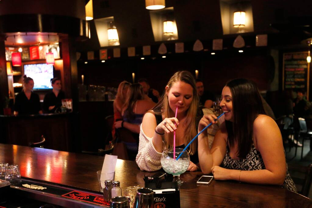 Sonoma State University students Kelsey Miller, left, and Gabriella Catalli share one of the signature Bowlas drinks at Tex Wasabi's in Santa Rosa, California on Wednesday, April 6, 2016. (Alvin Jornada / The Press Democrat)