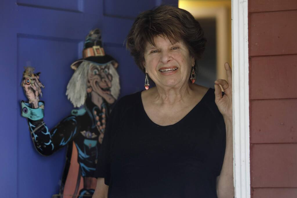 Ellyn Pelikan stands at her front door that is decorated with a paper Halloween witch from 1963 on Thursday, October 18, 2018 in Sebastopol, California . (BETH SCHLANKER/The Press Democrat)