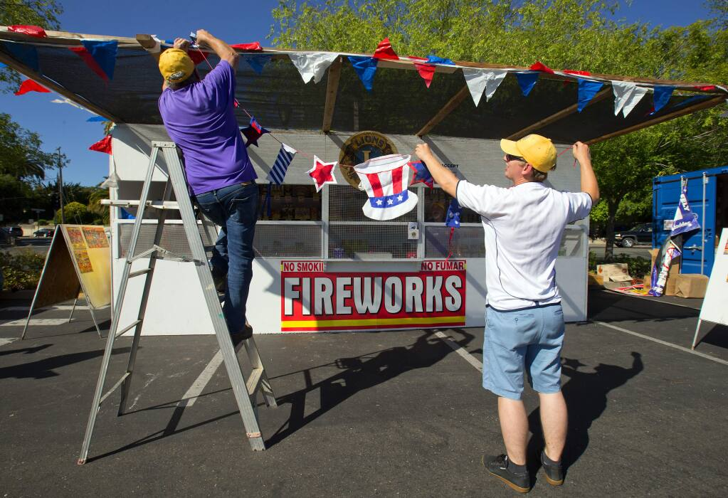 Don Canardo, left, and Mike Stanford hang Fourth of July banners on the Sebastopol Lions Club fireworks boot in the Safeway shopping center on the first day of legal fireworks sales in the county. (photo by John Burgess/The Press Democrat)