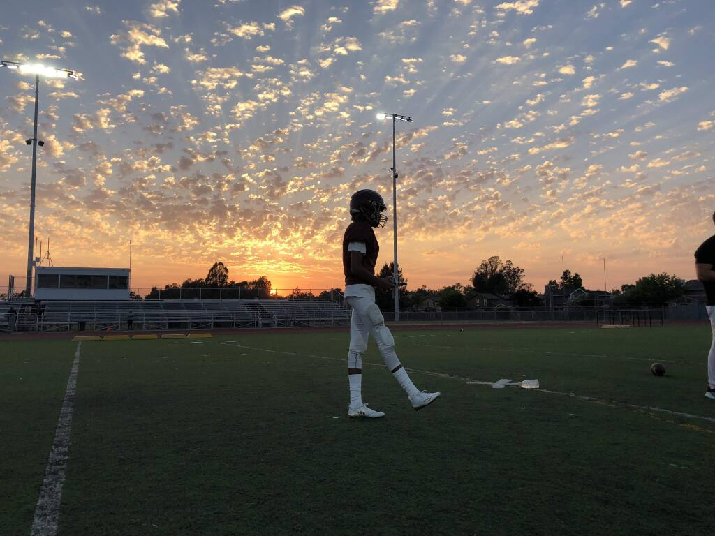 Junior quarterback Yonaton Isack walks across the Piner High School football field at a practice last week under the glow of new lights that will allow the Prospectors to play night games for the first time. (KERRY BENEFIELD/ PD)