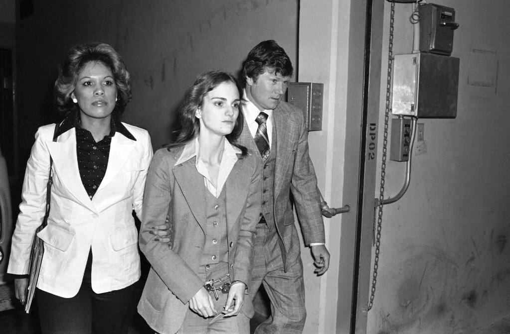 Accompanied by Deputy U.S. Marshal John Brophy, Patty Hearst, center, leaves the Federal Building in San Francisco, hours after her sentencing on a bank robbery conviction on April 12, 1976. Hearst was kidnapped and radicalized by the Symbionese Liberation Army in February 1974. (Associated Press)