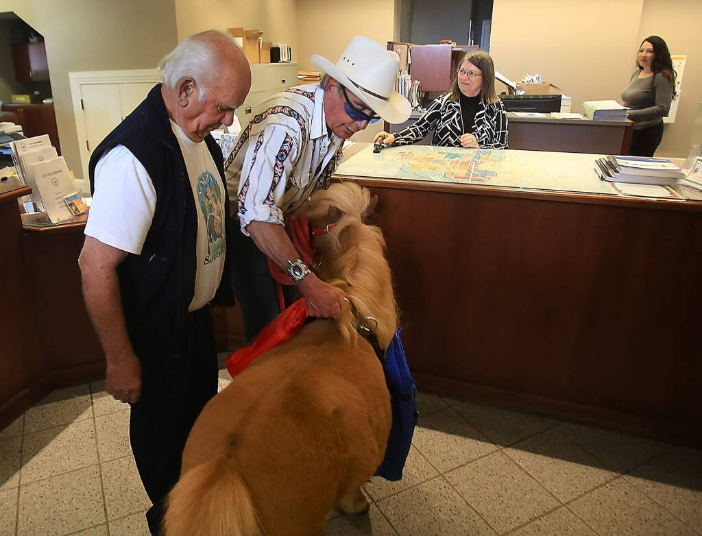 Gerald Marino, left and James Cannard remove pouched petitions from Cannard's horse Peanut Butter at Sonoma City Hall, Thursday April 14, 2016 after delivering petitions against the ban on leaf blowers in Sonoma. Accepting the petitions is Gay Johann, the Sonoma Assistant City Manager and City Clerk. (Kent Porter / Press Democrat) 2016