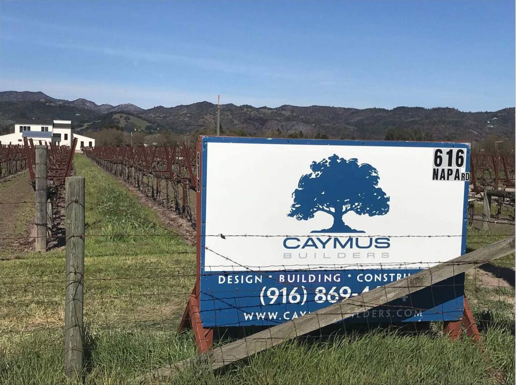 Exhibit 2 in Caymus Vineyard's suit against Caymus Builders et al: a sign for the Sonoma-based construction company posted in a vineyard, after the recent fires. This photograph was taken on Napa Rd. in Sonoma, signalling a building project. (Caymus Vineyards)