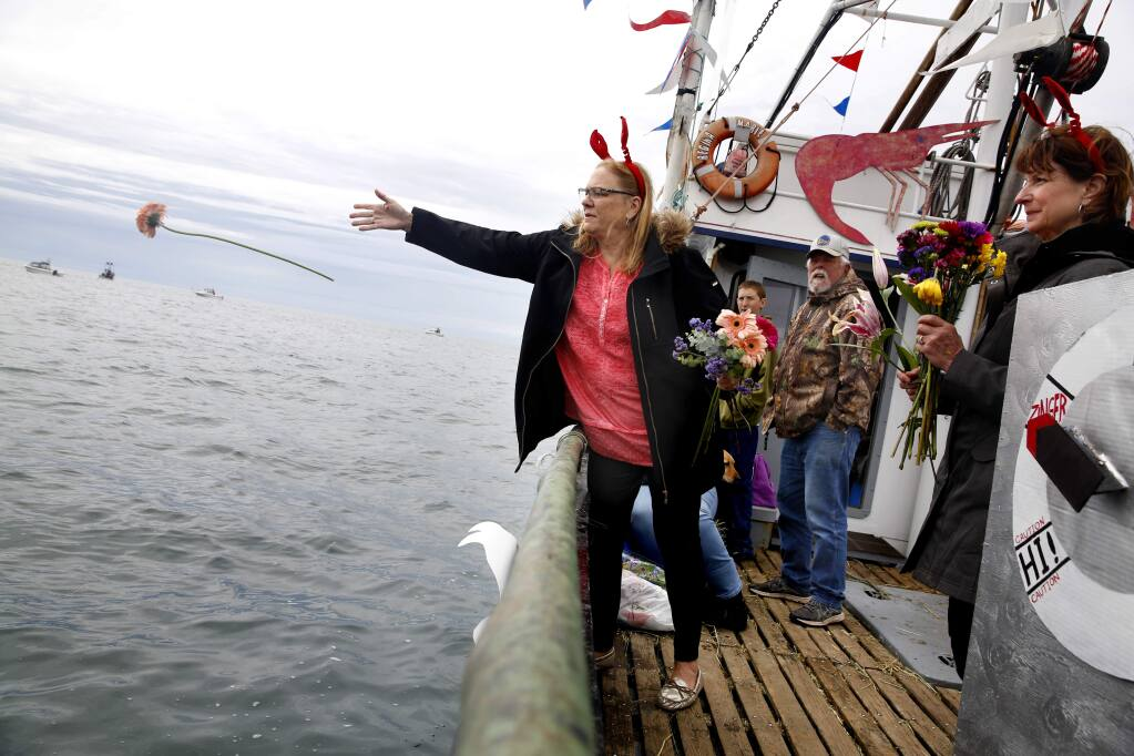 Karla Baiocchi throws flowers into the water during the Blessing of the Fleet as part of the Bodega Bay Fisherman's Festival on Sunday, April 10, 2016 in Bodega Bay, California . (BETH SCHLANKER/ The Press Democrat)