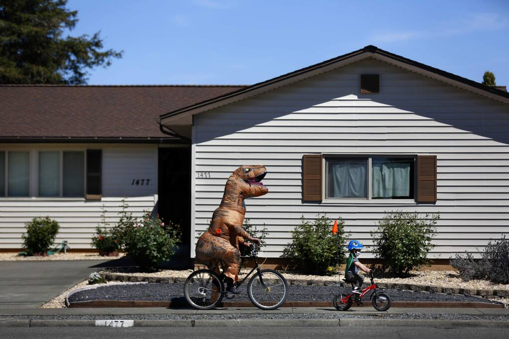Dan Sartin, dressed in an inflatable dinosaur costume and his son, Leo, 4, ride their bikes along Russell Ave in Santa Rosa, California on Tuesday, April 14, 2020. (BETH SCHLANKER/ The Press Democrat)