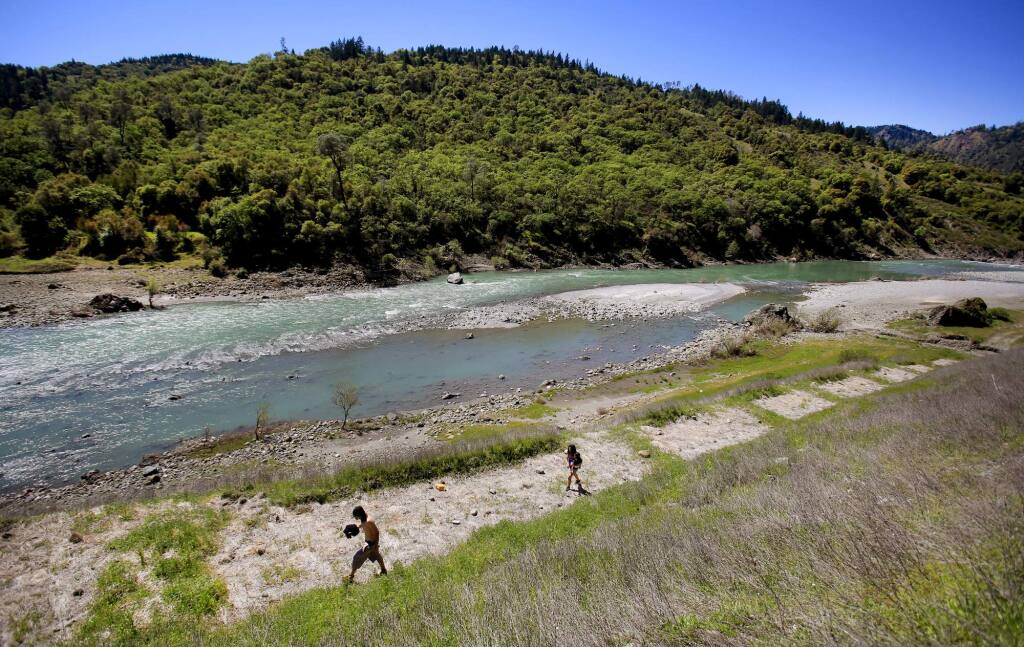 Chris Blazer, left and Melissa Garcia of San Francisco, head back to their vehicle after a day of sunning along the banks of the Eel River in Dos Rios on Wednesday, April 7, 2016. (KENT PORTER/ PD FILE)