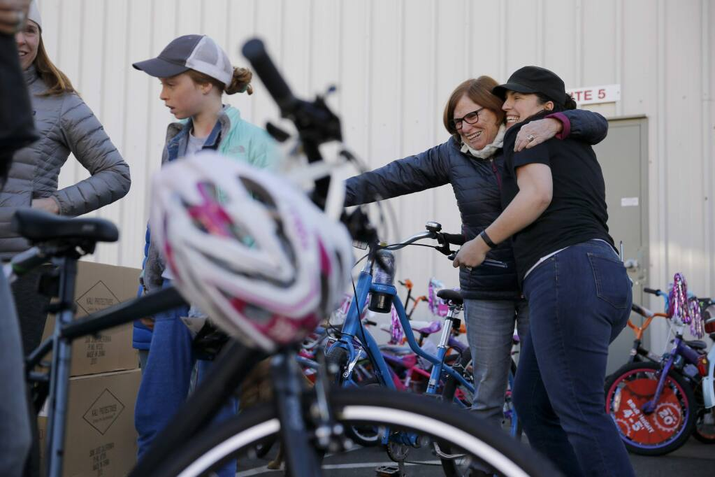 Glen Ellen resident and fire victim Lauri Dorman embraces Carolyn Thompson, right, the co-owner of Bicycle Brustop, after receiving a bike that Thompson built, during a bicycle giveaway event on Sunday, December 10, 2017 in Sonoma, California . (BETH SCHLANKER/The Press Democrat)