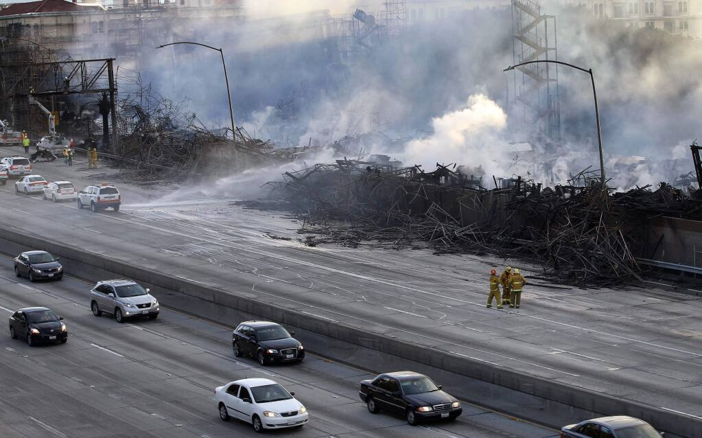 Los Angeles firefighters and state highway workers watch as an apartment building under construction smolders after a massive fire along State Route 110 that engulfed the site near downtown Los Angeles on Monday, Dec. 8, 2014. Crews battled two large fires in Los Angeles early Monday, including one downtown that closed portions of two major freeways and blanketed the area in ash and heavy smoke. (AP Photo/Nick Ut)