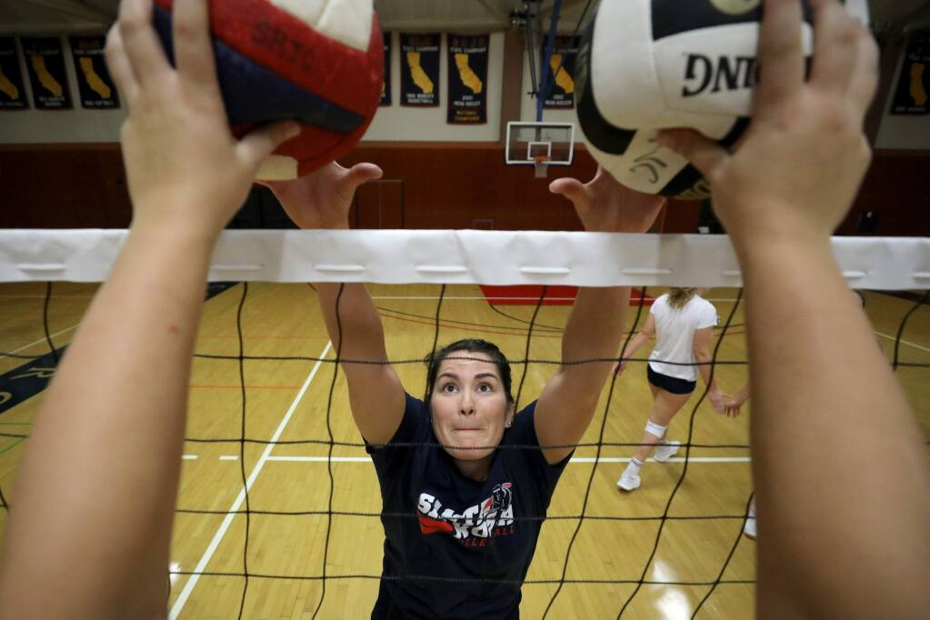 Jessica Crawford does a blocking drill as she practices with the volleyball team at Haehl Pavilion on the Santa Rosa Junior College campus in Santa Rosa on Monday, September 23, 2019. (BETH SCHLANKER/ The Press Democrat)