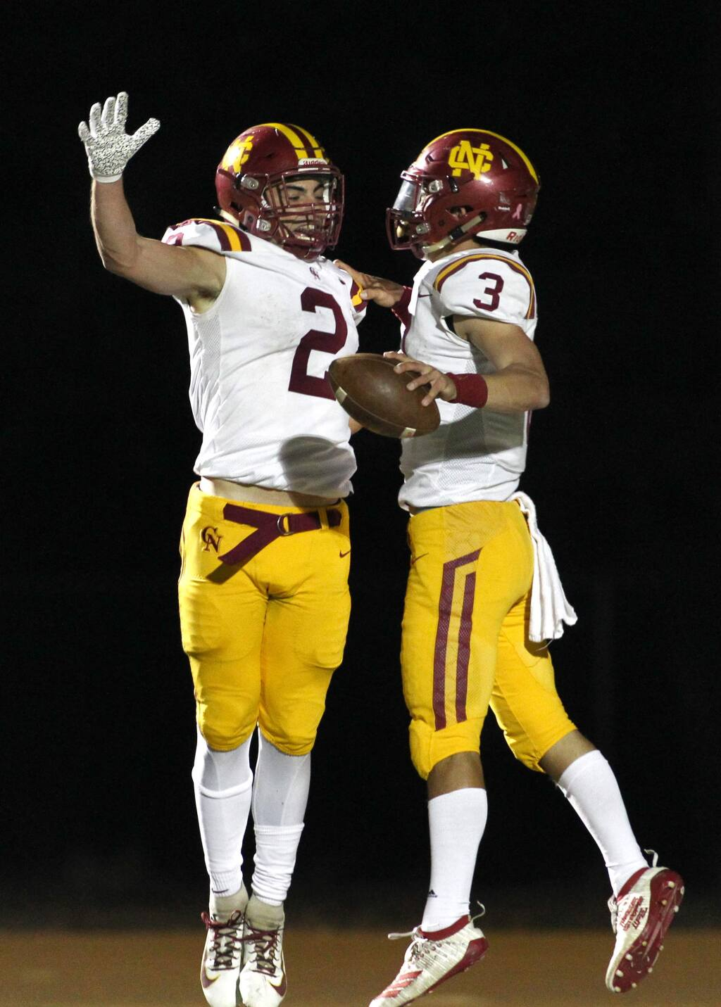 Cardinal Newman's Giancarlo Woods (2) and Jackson Pavitt (3) celebrate a touchdown by Pavitt against Maria Carrillo in Santa Rosa on Monday, Nov. 4, 2019. (Photo by Darryl Bush / For The Press Democrat)