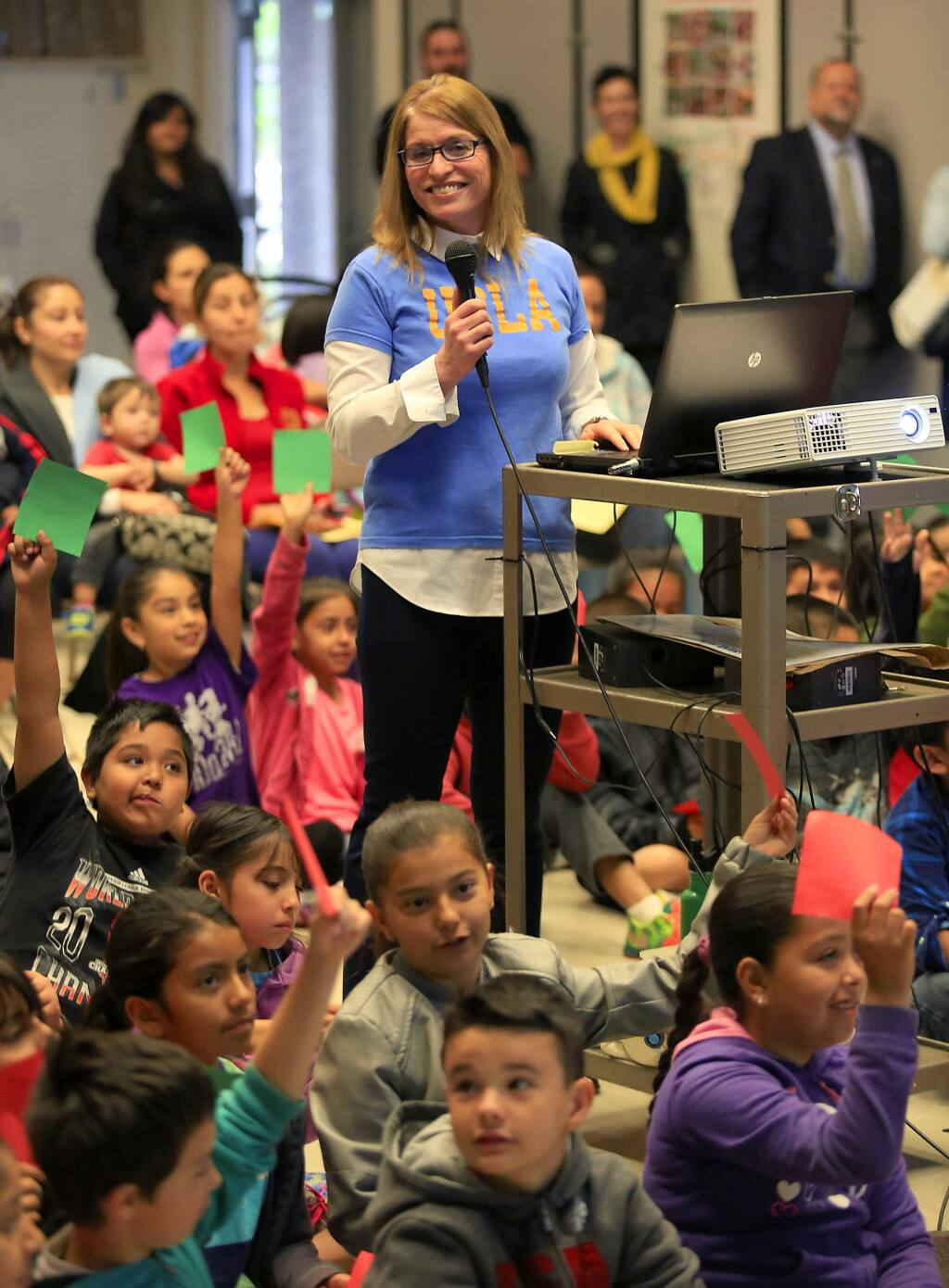 Santa Rosa City Schools board member Jenni Klose quizzes second- and third-grade Helen Lehman elementary school students about professions needing a college degree. Klose founded The College Tee Project to encourage young students to attend college. (JOHN BURGESS / The Press Democrat)