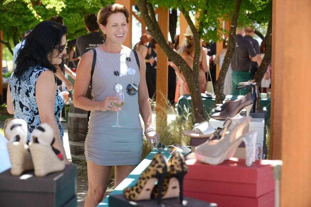 Neda Lohrer, left and Anne-Marie Failla looking over the shoe selection at Gina's Boutique booth during Wine Women & Shoes event held Saturday at Clos Du Bois Winery in Geyserville, California. The event benefits Healthcare Foundation Northern Sonoma County. June 23, 2018.(Photo: Erik Castro/for The Press Democrat)