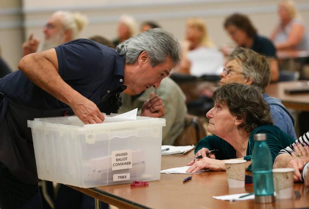 Juan Diaz, storekeeper for the Sonoma County Registrar of Voters office, talks with Sarah DeWitt during voter precinct volunteer training, in Santa Rosa on Thursday, February 27, 2020. (Christopher Chung/ The Press Democrat)