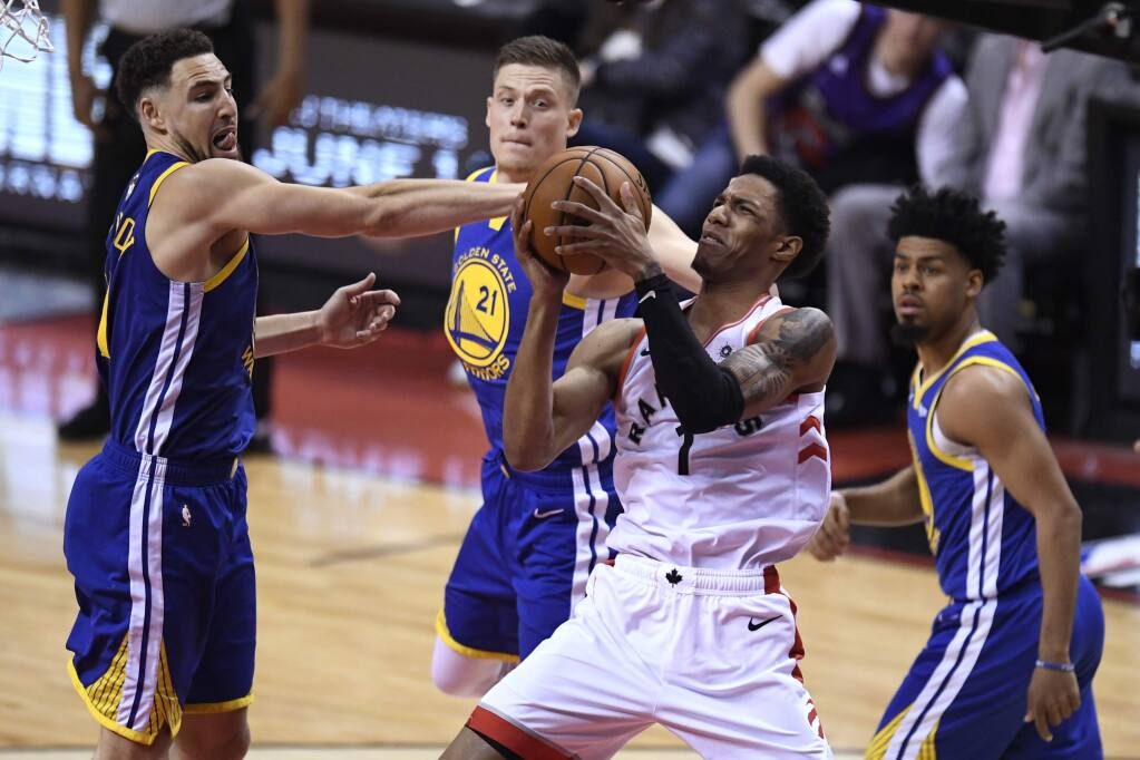 Toronto Raptors guard Danny Green (14) works against Golden State Warriors guard Klay Thompson (11) during the second half of Game 1 of the NBA Finals, Thursday, May 30, 2019, in Toronto. (Frank Gunn/The Canadian Press via AP)