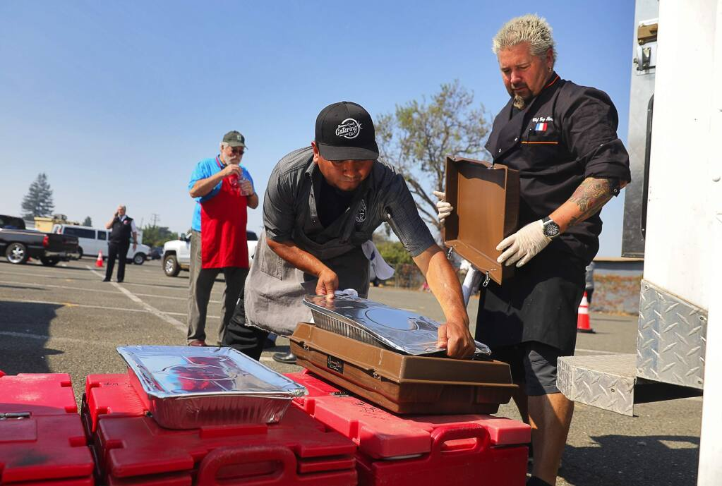 Celebrity chef Guy Fieri, right, and Cesar Orozco pack bins with food to be delivered to area evacuation centers by the Salvation Army, behind the Veterans Memorial building in Santa Rosa on Thursday, October 12, 2017. (Christopher Chung/ The Press Democrat)