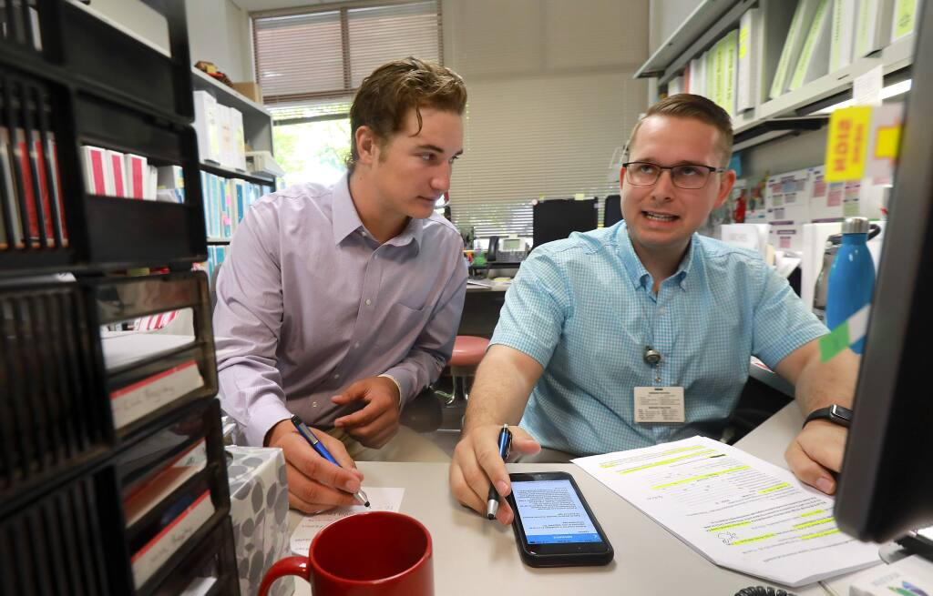 Intern Alec Rennard, left, works with Clinical Research Coordinator Anthony Blackburn to identify possible candidates for breast cancer clinical trials in the St. Joseph Health cancer care center in Santa Rosa. Renaud is pitching this summer for the Healdsburg Prune Packers before returning to Michigan University in the fall. (John Burgess / The Press Democrat)