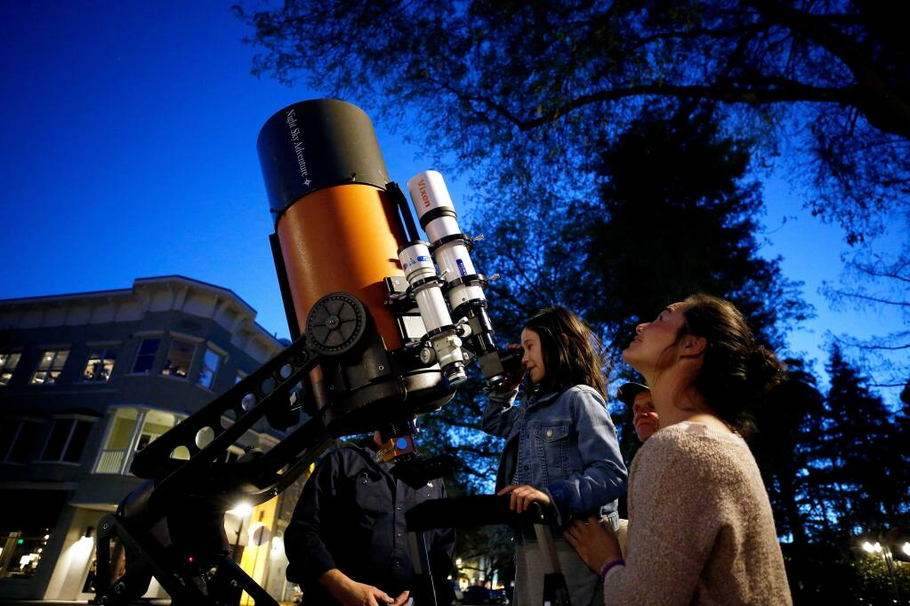 Heavenly Swendsen, right, of Campbell looks into the sky while he daughter Pascale, 7, peers at the moon through one of the telescopes set up by Dan and Bill Gordon of Night Sky Adventure, in Healdsburg, California, on Friday, March 15, 2019. (Alvin Jornada / The Press Democrat)