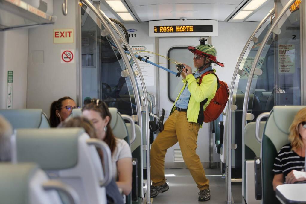 Steve Bush unhooks his bike on the SMART train as he arrives at his destination on Friday, September 29, 2017 in Santa Rosa, California . (BETH SCHLANKER/The Press Democrat)