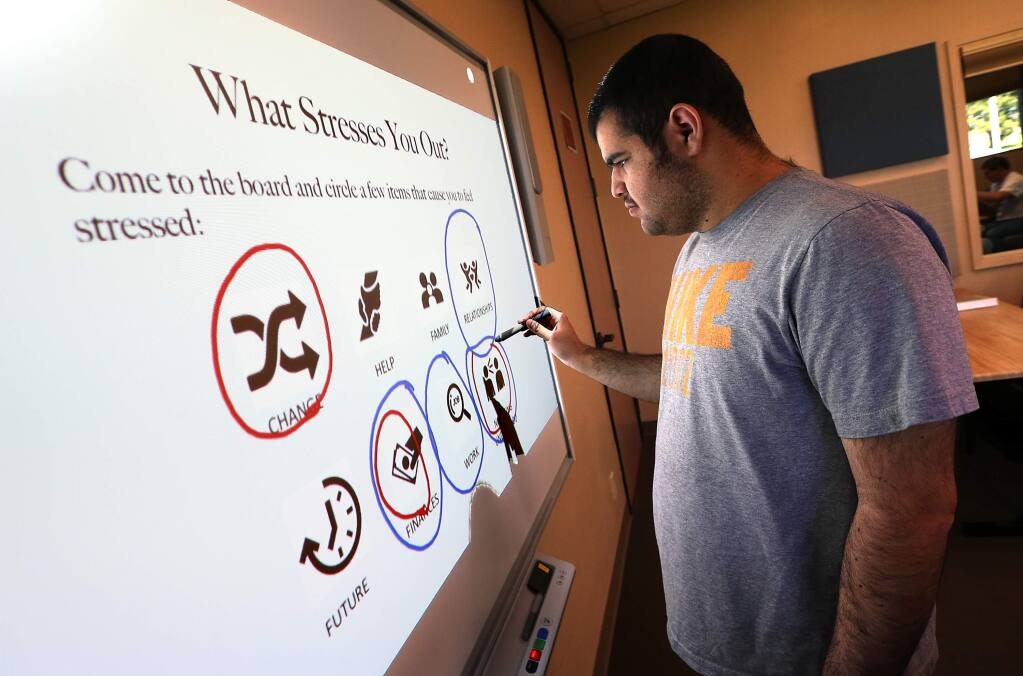 Client Isa House, 19, circles some of the things that cause him stress on a 'smart board' in the Becoming Independent Passport to Independence program for people with autism. (JOHN BURGESS / The Press Democrat)
