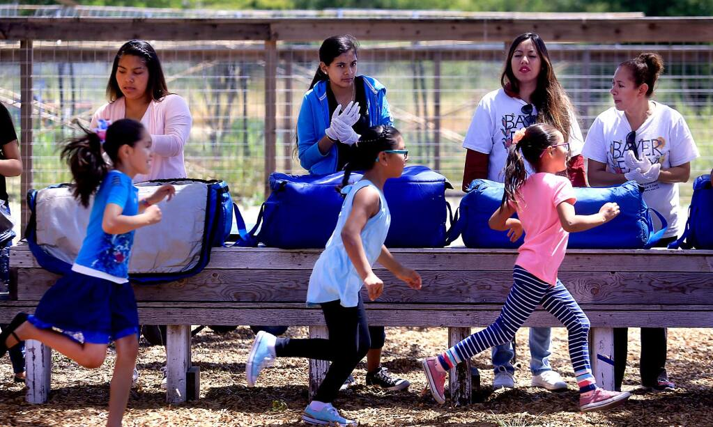 Idolina Cervantes, Flor Becerra, Perla Acuna and Paula Hernandez prepare to serve lunch from the Redwood Empire Food Bank at the Bayer Farm in Santa Rosa on Monday, June 5, 2017, to, from left in the foreground, Yajaira Hernandez, Mary Diaz and Tania Hernandez. (KENT PORTER/ PD)