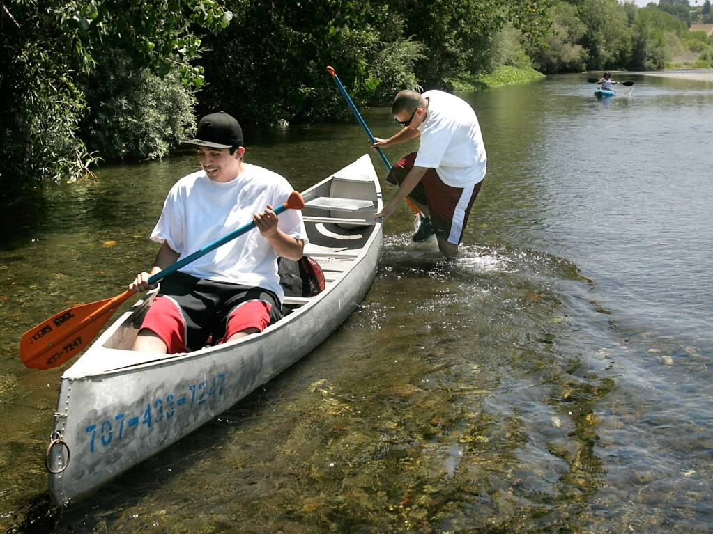 (File photo) David Narvaez of San Francisco pushes his friend Hugo Gomez through the shallow waters of the Russian River east of Healdsburg (2009)